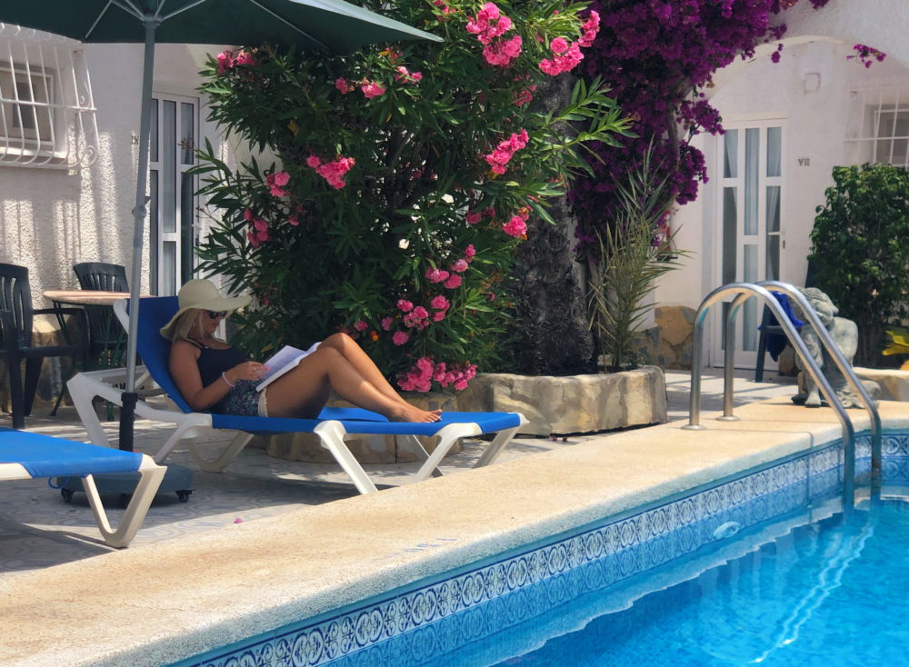 A guest reading a booking and resting by the swimming pool at La Crisalida Retreats, health and wellbeing retreat, Spain